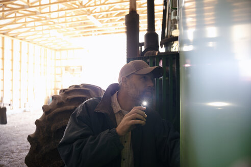 Male farmer with cell phone flashlight examining tractor in barn - HEROF33586