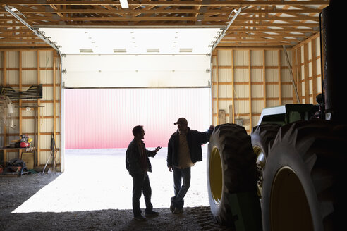 Male farmers talking at tractor inside barn - HEROF33589