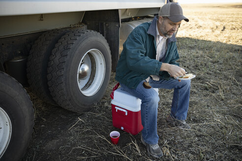Male farmer eating lunch on cooler on farm - HEROF33619
