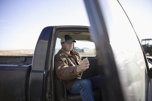 Male farmer using laptop in truck on sunny farm - HEROF33640
