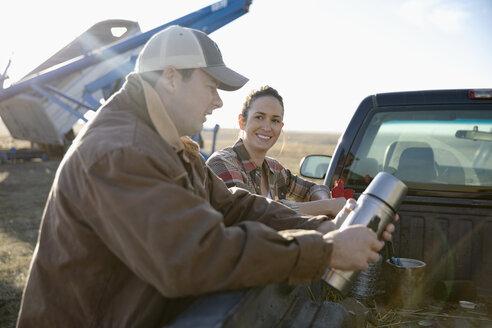 Farmer couple taking coffee break at truck on farm - HEROF33643