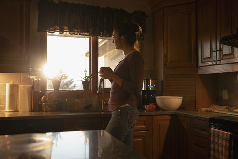 Woman drinking coffee in sunny morning kitchen - HEROF33655