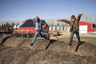 Brothers jumping on hay bales on sunny farm - HEROF33685