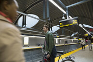 Businessman with bicycle on subway station platform - HEROF33736