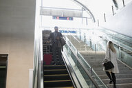 Businessman with suitcase descending escalator at train station - HEROF33739