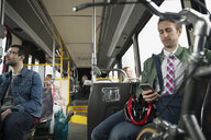 Businessman with bicycle texting on bus - HEROF33745