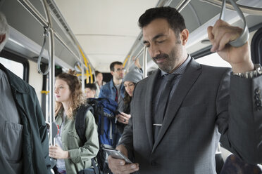 Businessman texting with cell phone standing on bus - HEROF33754