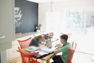 Brothers and sister doing homework at dining table - HEROF33778
