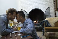 Affectionate homosexual couple face to face next to fireplace in living room - HEROF33865