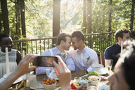 Affectionate homosexual couple on balcony at wedding reception - HEROF33877
