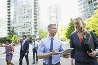 Businessman and businesswoman using digital tablet on city street - HEROF33889