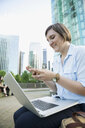 Businesswoman with laptop texting with cell phone in city - HEROF33940