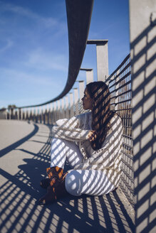 Young woman sitting on a bridge - RSGF00167