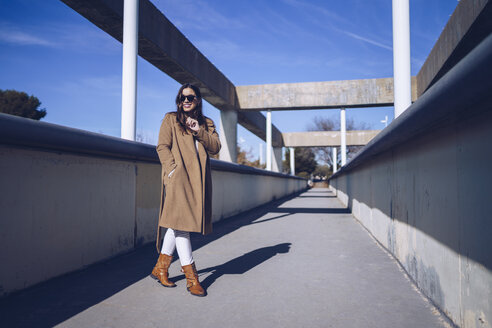 Smiling young woman wearing coat and sunglasses on a bridge - RSGF00170