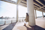 Young woman leaning against a column at a lake - RSGF00176