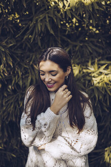 Portrait of smiling young woman at a plant - RSGF00182