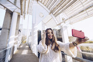 Happy young woman taking a selfie on a bridge - RSGF00185