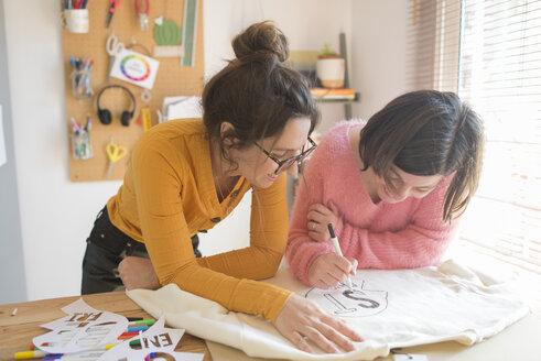 Two women drawing stencils for printing sweatshirts - SKCF00578