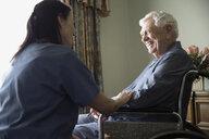 Home caregiver talking to smiling senior man in wheelchair - HEROF33967