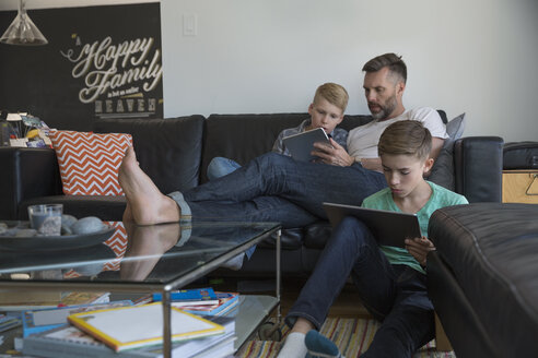 Father and sons relaxing with digital tablets in living room - HEROF34030