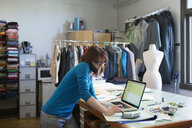 Dressmaker using laptop and talking on cell phone at workbench - HEROF34075