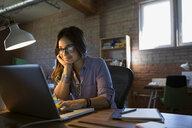 Female designer using laptop at desk in office - HEROF34123
