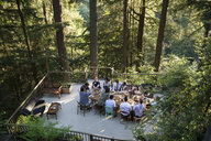 Friends eating at long dining table on balcony at wedding reception - HEROF34165