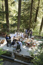 Friends talking around long dining table on balcony in woods at wedding reception - HEROF34174