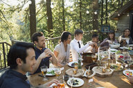Friends dining around long dining table on balcony at wedding reception - HEROF34180