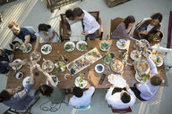 Friends dining around long dining table at wedding reception - HEROF34183