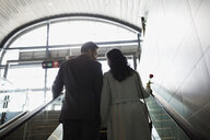 Couple ascending escalator at train station - HEROF34186