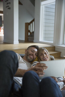Couple relaxing using digital tablet on sofa in living room - HEROF34198