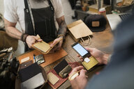 Customer using credit card reader in leather shop - HEROF34204