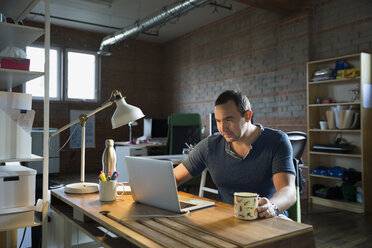 Creative businessman working at laptop in office - HEROF34213