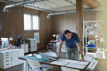 Designer reviewing plans on office desk - HEROF34216