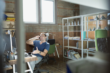 Creative businessman talking on cell phone in office - HEROF34219