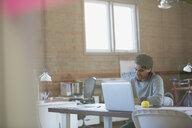Designer working at laptop in office - HEROF34228