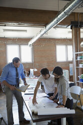 Designers reviewing and discussing plans in office - HEROF34243