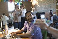 Coworker serving surprised creative businessman birthday donut with sparkler - HEROF34273