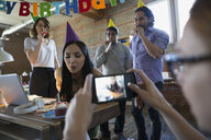 Coworker photographing businesswoman blowing out birthday candle in office - HEROF34276