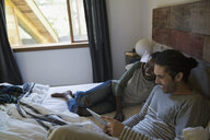 Couple using digital tablet on bed - HEROF34351