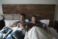 Comfortable homosexual couple using digital tablet and cell phone in bed - HEROF34354
