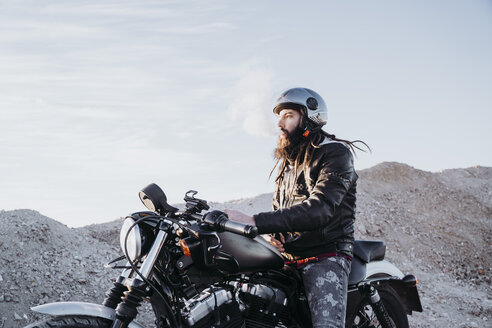 Bearded man with dreadlocks sitting on motorbike smoking electronic cigarette - OCMF00350