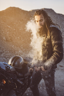 Portrait of bearded biker with dreadlocks  smoking electronic cigarette - OCMF00353