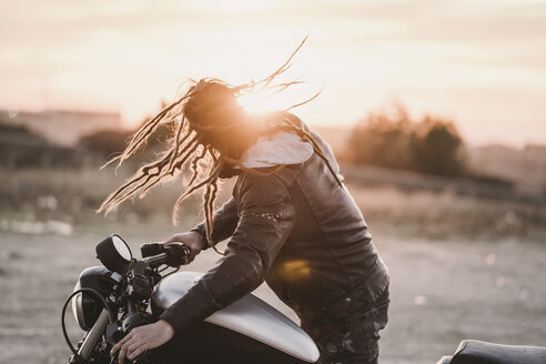 Biker tossing his dreadlocks at sunset - OCMF00356