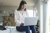 Smiling young woman sitting on table at home using laptop - UUF16960