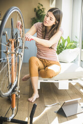 Young woman reparing bicycle at home - UUF17014