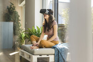 Happy young woman sitting at the window at home wearing VR glasses - UUF17020