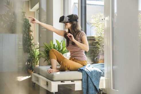 Young woman sitting at the window at home wearing VR glasses - UUF17023