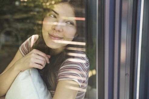 Portrait of smiling young woman behind windowpane - UUF17026